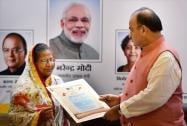 Union Finance Minister Arun Jaitley hands over a policy to a beneficiary