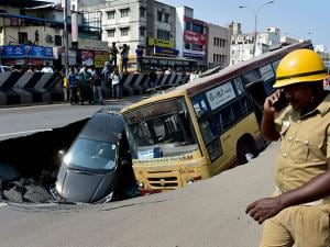 A car and bus sink into a huge crater formed after a portion of the road caved in at the arterial Anna Salai