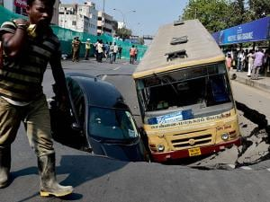 car and bus sink into a huge crater formed after a portion of the road caved in at the arterial Anna Salai