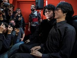 Robotics scientist Hiroshi Ishiguro, left, poses with 'Geminoid'