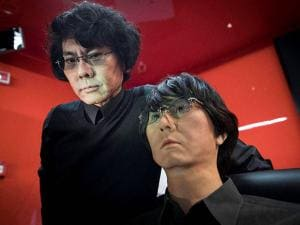 Robotics scientist Hiroshi Ishiguro  poses with 'Geminoid'