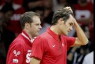 Roger Federer holds his hair followed by coach Severin Luthi