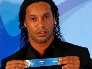 Brazil's soccer player Ronaldinho holds a paper that reads Japan during the draw for the men's Olympic football tournament in Rio de Janeiro, Brazil.
