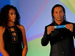 Janeiro  Brazil's soccer player Ronaldinho holds a paper that reads Honduras, as he's flanked by former soccer player Aline Pellegrino during the draw for the men's Olympic football tournament