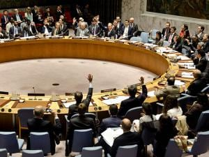 United Nations Security Council members show hands for a vote on a resolution condemning Syria's use of chemical weapons