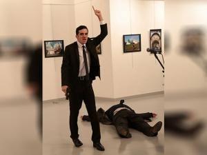 A gunman gestures near to Andrei Karlov, the Russian Ambassador to Turkey