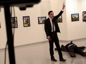 A man gestures near to the body of a man at a photo gallery in Ankara