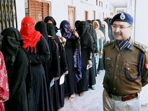 Police personnel guarding a polling station in Saharanpur as voters queue up to vote