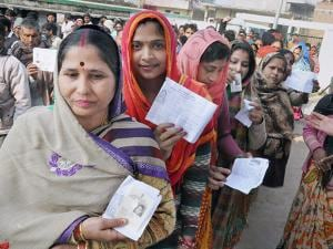 Voters stand in queue to cast their vote during the second phase of UP assembly polls