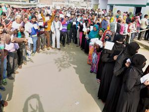 Voters stand in queue to cast their vote during the second phase of UP assembly polls in Moradabad