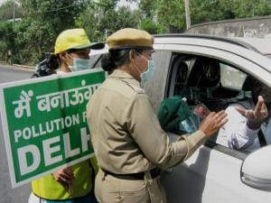 Volunteers present red roses to an offender of odd-even scheme at Gurgaon border in New Delhi on Friday. The second phase of the scheme was rolled out in the national capital.