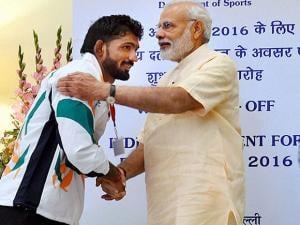 Narendra Modi greets wrestler Yogeshwar Dutt at a warm send-off ceremony
