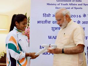 Narendra Modi signing on the hockey stick of Deepika Thakur at a warm send-off ceremony