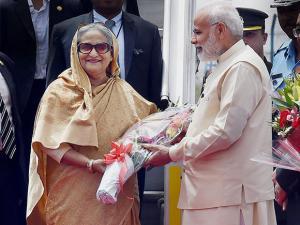 Prime Minister Narendra Modi presents a bouquet to Bangladesh PM Sheikh Hasina