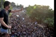 Bollywood actor Shah Rukh Khan greets a huge crowd of fans gathered outside