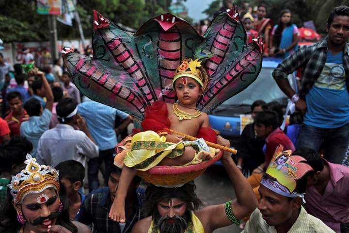 Bangladeshi Hindu, devotee, carries, head, child dressed,  Hindu god, Krishna, basket, procession, celebrate, Janmashtami,  Krishna's, birth day, Dhaka