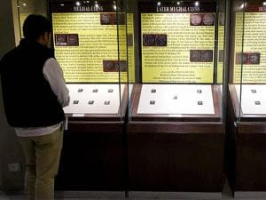 A visitor looks at a collection of coins from Mughal-era