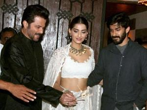 Anil Kapoor holding a sparkler as  Sonam Kapoor and Harshvardhan Kapoor