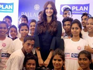 Sonam Kapoor poses for a photo with with children at an event