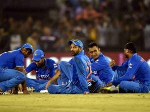 Indian Cricketers sit in the ground