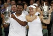 Leander Paes of India and Martina Hingis of Switzerland hold up the trophies