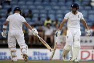 England's captain Alistair Cook and teammate Jonathan Trott touch bats to celebrate runs
