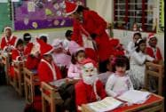 School students dressed as Santa Claus ahead of Christmas day celebrations