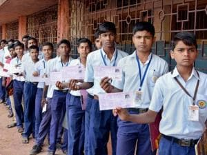 Students show their admission cards in queue outside an examination centre during the Maharashtra State Board of Secondary School Certificate Education [SSC] examinations, in Karad