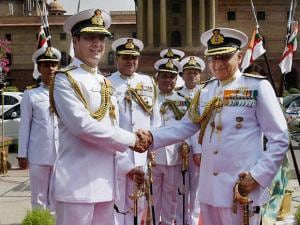 India's new Naval Chief, Admiral Sunil Lanba  shaking hand with outgoing chief Robin K Dhowan before taking over as Navy chief and inspecting the Guard of Honour