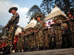 Nepalese army soldiers give a guard of honor during the cremation of Nepalese prime minister Sushil Koirala, on the banks of the Bagmati River in Kathmandu