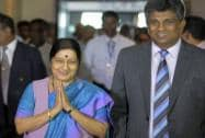 Indian Foreign Minister Sushma Swaraj greets officials as she walks with Sri Lankan Deputy Foreign Minister Ajith Perera