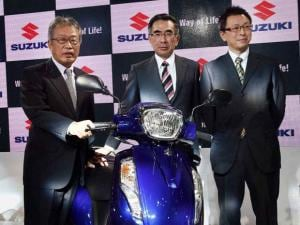 Suzuki Motorcycles officials pose with a scooter at their stall