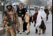 Pakistani parents escort their children outside a school