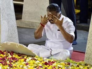 Tamil Nadu Chief Minister O Panneerselvam sitting in front of late J Jayalalithaa's burial site at the Marina Beach in Chennai
