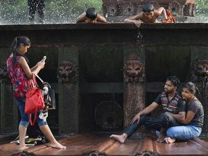 People enjoy at a water fountain at the India  as the mercury rises in New Delhi01