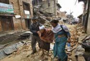 An elderly injured woman is taken to her home after treatment in Bhaktapur near Kathmandu
