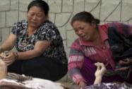 Unidentified relatives mourn near the bodies of those killed in earthquake at a hospital