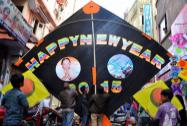 Kitemakers hold a giant kite carrying new year greetings