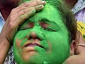 A Trinamool Congress supporter is daubed in green color by another supporter as as they celebrate the party's thumping victory in West Bengal Assembly eections in Kolkata