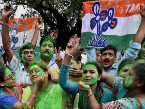 A Trinamool Congress supporter is daubed in green color by another supporter as as they celebrate the party's thumping victory in West Bengal Assembly eections in Kolkata (2)
