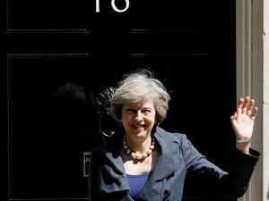 Britain's Home Secretary Theresa May waves to the media as she leaves after attending a cabinet meeting