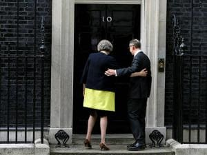 Theresa May and her husband Philip May stand on the steps of 10 Downing Street