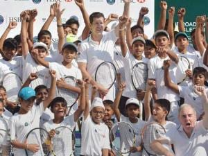 Former British tennis player Tim Henman poses for media with young tennis players at the MSLTA, in Mumbai during a press conference of Road to Wimbledon in India