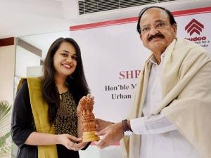 Tina Dabi being felicitated by Union Urban Development Minister Venkaiah Naidu during a programme of HUDCO