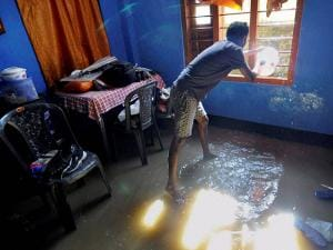 A man throwing away water from his house in the flooded Rupnagar area after heavy downpour in Guwahati