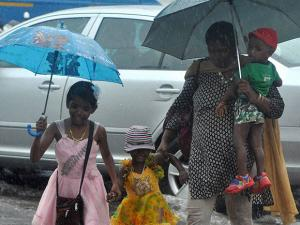 A woman, holding umbrella, walks with ker kids at a road during the first monsoon rains in Kochi