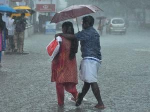 People, holding umbrellas, walk at a road during the first monsoon rains in Kochi