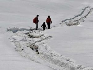 A tourist couple with their kid at Gulmarg ski resort in district Baramulla