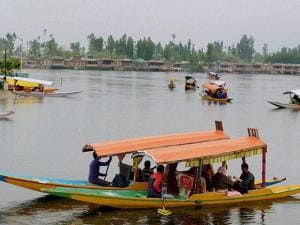Tourists ride Shikaras as they enjoy the cool weather at Dal Lake in Srinagar