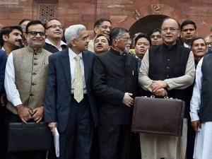 Finance Minister Arun Jaitley  stands outside his office at North Block holding the briefcase containing the Union budget for 2017 and is flanked by MoS Arjun Meghwal  and Santosh Gangwar